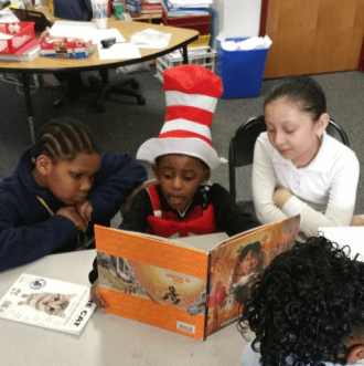Children sitting around a table reading a book