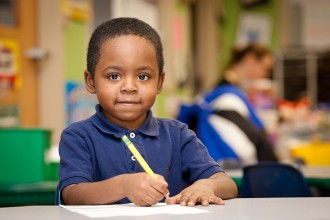 A child holding a pencil to paper