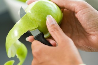 An apple being peeled with a knife