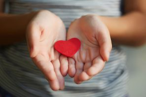 A small heart shaped object between a person's hands