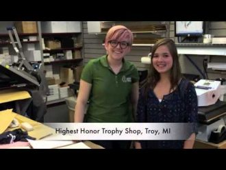 Two students interning and posing at Highest Honor Trophy Shop