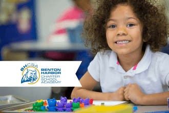 A student smiling in a promotion for Benton Harbor Charter School Academy