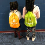 "2 young Bradford students showing off their new backpacks - ""Giving Pack"""