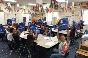 "Bradford students in class all showing off their new ""Giving Pack"" backpacks"