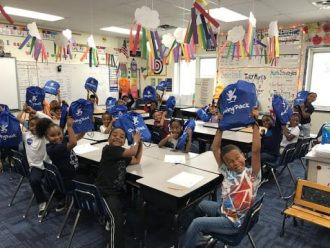 """Bradford students in class all showing off their new """"Giving Pack"""" backpacks"""