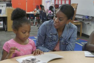 Teacher helping a student read
