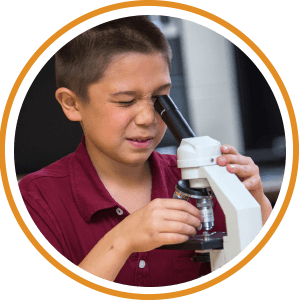 child looking through microscope