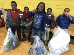 Dove Academy of Detroit students with their gift from Operation Warmth and Comfort