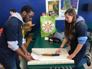 Two West Michigan Academy of Environmental Science students cutting wrapping paper