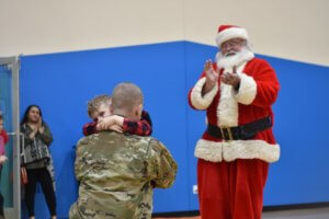BCMA Student hugging his military father with santa clapping in the background