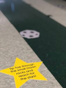 Star sticker on the ground that reads, tip toe through the small moon rocks and reach for the stars
