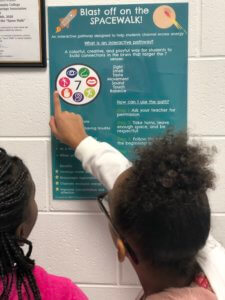 Two female students looking at the space walk poster