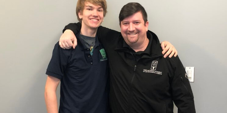 WMAES student, Randy standing arm in arm with Josh Miller, WMAES Dean of Stuents